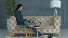 Säker kvinna som hemma arbetar på bärbara datorn lager videofilmer