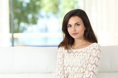 Säker kvinna som hemma poserar att sitta på en soffa royaltyfri bild