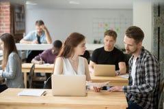 Säker kvinnlig arbetare som förklarar företagsplan till den manliga colleaguen royaltyfria foton
