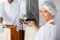 Säker kvinnlig bagare Using Cutting Machine i bageri arkivfoton