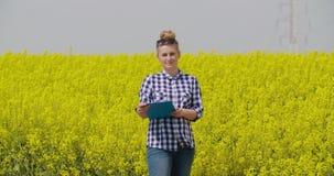 Säker kvinnlig bonde Writing In Clipboard på rapsfröfältet arkivfilmer