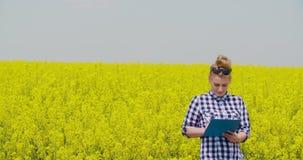 Säker kvinnlig bonde Writing In Clipboard på rapsfröfältet stock video