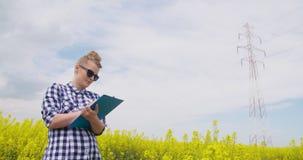 Säker kvinnlig bonde Writing In Clipboard på rapsfröfältet lager videofilmer