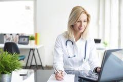 Säker kvinnlig doktor på kontorsskrivbordet arkivfoton