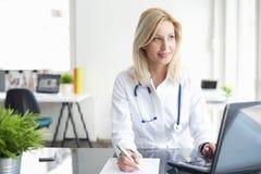 Säker kvinnlig doktor på kontorsskrivbordet royaltyfri fotografi