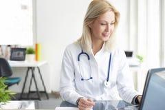 Säker kvinnlig doktor på kontorsskrivbordet fotografering för bildbyråer