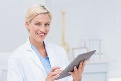 Säker kvinnlig doktor som använder den digitala minnestavlan Arkivbild