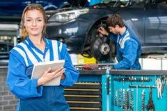 Säker kvinnlig mekaniker With Maintenance Checklist på garaget arkivbild