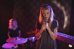 Säker kvinnlig sångare med handelsresanden som utför på upplyst etapp i nattklubb Royaltyfri Foto