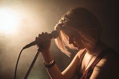 Säker kvinnlig sångare med mikrofonen i upplyst nattklubb Arkivbilder