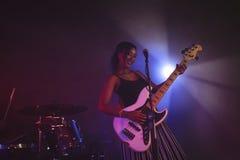 Säker kvinnlig sångare som spelar gitarren i upplyst nattklubb Royaltyfria Bilder
