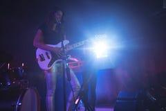 Säker kvinnlig sångare som spelar gitarren på upplyst etapp i nattklubb Royaltyfri Fotografi