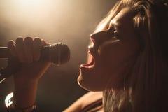 Säker kvinnlig sångare som utför i upplyst nattklubb Royaltyfri Foto