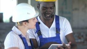Säker kvinnlig tekniker eller arkitekt som diskuterar konstruktionsfrågor med den manliga kollegan lager videofilmer