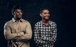 Säker le indier som två bär tillfällig kläder som poserar med korsade armar och från sidan ser arkivfoto