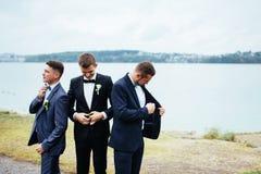 Säker le stilig brudgum i svart dräkt med groomsma två royaltyfri fotografi