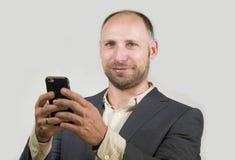 Säker lyckad affärsman som använder mobiltelefonen som har att göra online-affär med att le för mobiltelefon som är gladlynt i fö fotografering för bildbyråer