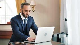 Säker lyckad manlig affärsmanmaskinskrivningtext eller prata på tangentbordet genom att använda bärbar datorPC arkivfilmer