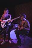 Säker man och kvinna som utför med gitarrer royaltyfria foton