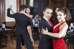 Säker man och kvinna som utför tango i restaurang Arkivbilder