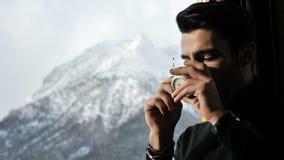Säker man som dricker kaffe på landskap lager videofilmer