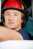 Säker manlig brandman Sitting In Firetruck Arkivfoton