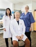 Säker manlig doktor Sitting By Team In Clinic royaltyfria bilder