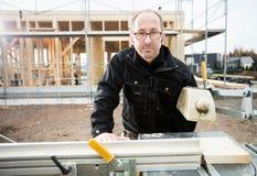 Säker manlig snickare Using Table Saw som klipper plankan Royaltyfria Bilder