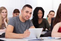 Säker manlig student som rymmer den digitala minnestavlan på skrivbordet arkivbild