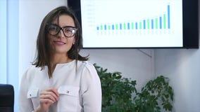 Säker mogen affärskvinna som i regeringsställning står Kvinnlig chef i regeringsställning som ser kameran och att le långsam röre lager videofilmer