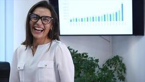 Säker mogen affärskvinna som i regeringsställning står Kvinnlig chef i regeringsställning som ser kameran och att le långsam röre arkivfilmer
