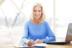 Säker mogen affärskvinnastående med bärbara datorn royaltyfri bild