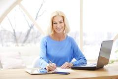 Säker mogen affärskvinnastående med bärbara datorn arkivbild