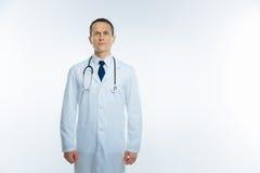 Säker mogen doktor i det vita laget över vit bakgrund arkivbild