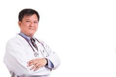 Säker mognad asiatisk doktor med vikta armar royaltyfri fotografi