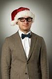 Säker nerd i den Santa Claus hatten och flugan fotografering för bildbyråer