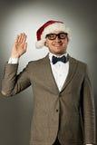Säker nerd i den Santa Claus hatten och flugan royaltyfri bild