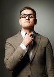 Säker nerd i glasögon som justerar hans fluga arkivfoton