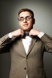 Säker nerd i glasögon som justerar hans fluga royaltyfria foton