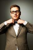 Säker nerd i glasögon som justerar hans fluga royaltyfri foto