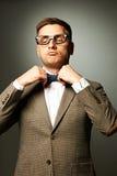 Säker nerd i glasögon som justerar hans fluga fotografering för bildbyråer