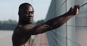 Säker och ilsken afrikansk amerikanman som ser den utomhus- kameran - Anseende för man för droghandlare, fånge- eller brottsling arkivfilmer