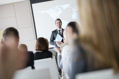 Säker offentlig högtalare som ser åhörare som applåderar under seminarium Royaltyfria Bilder
