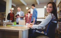 Säker rörelsehindrad affärskvinnahandstil på skrivbordet Arkivfoto