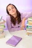 Säker studentflicka mellan buntar av böcker Royaltyfri Foto