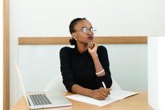 Säker svart affärskvinna i exponeringsglas som rymmer hakan som bort i regeringsställning ser på skrivbordet med notepaden och bä arkivbilder