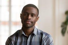 Säker svart man som inomhus ser kameran fotografering för bildbyråer