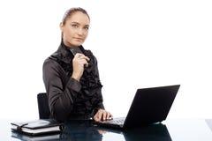 Säker ung affärskvinna på skrivbordet Royaltyfri Foto