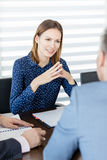 Säker ung affärskvinna som diskuterar med manliga kollegor i bräderum Royaltyfri Fotografi