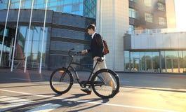 Säker ung affärsman som går med cykeln på gatan i stad royaltyfri fotografi